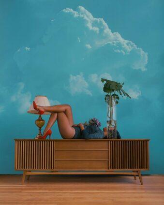 Eine Person liegt mit überschlagenen Beinen auf einem Schrank vor einem Himmel.