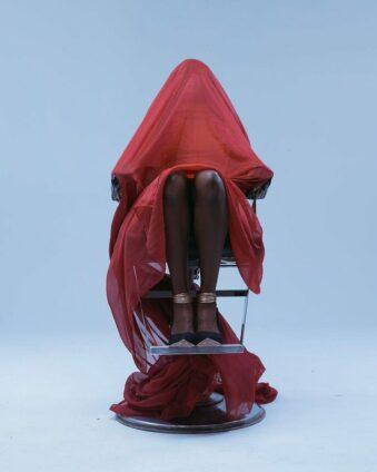 Mit rotem Tuch abgedeckte Person sitzt auf einem Frisierstuhl.