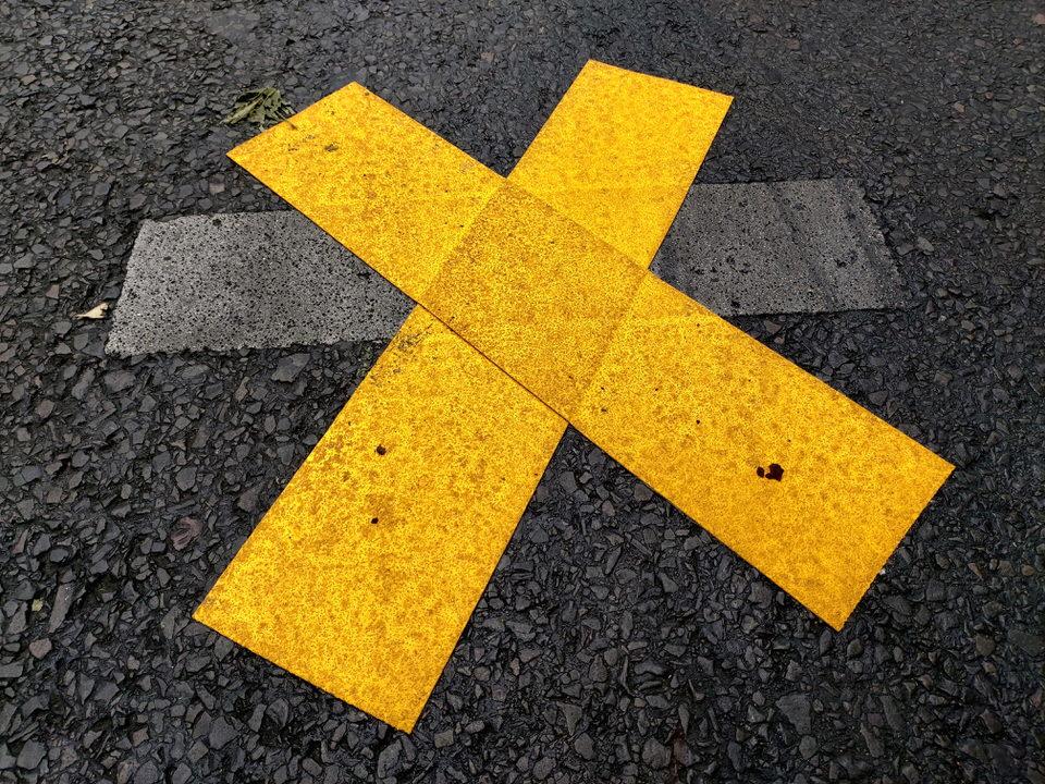 Ein gelbes Kreuz auf der Straße
