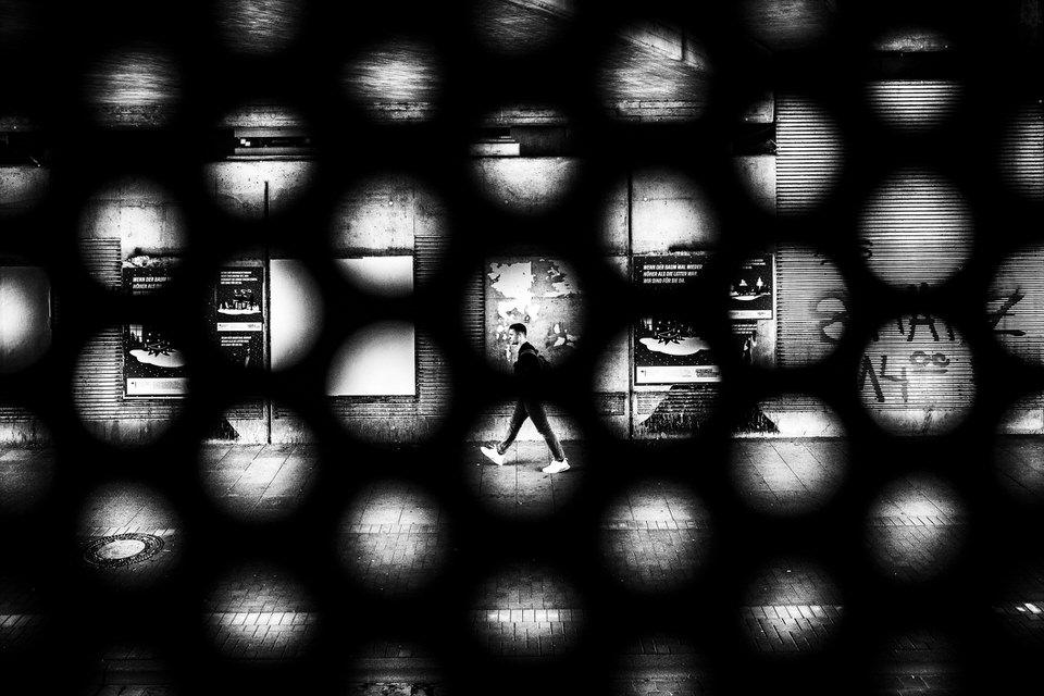 Passant durch Löcher in einem Mauer fotografiert
