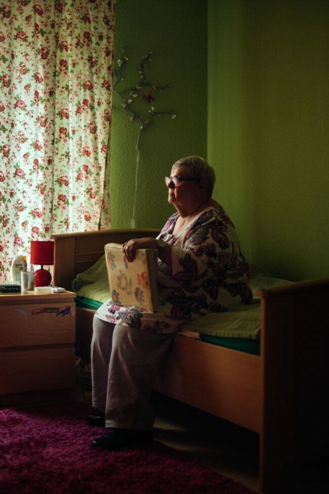 Frau sitzt mit einem Album auf dem Bett