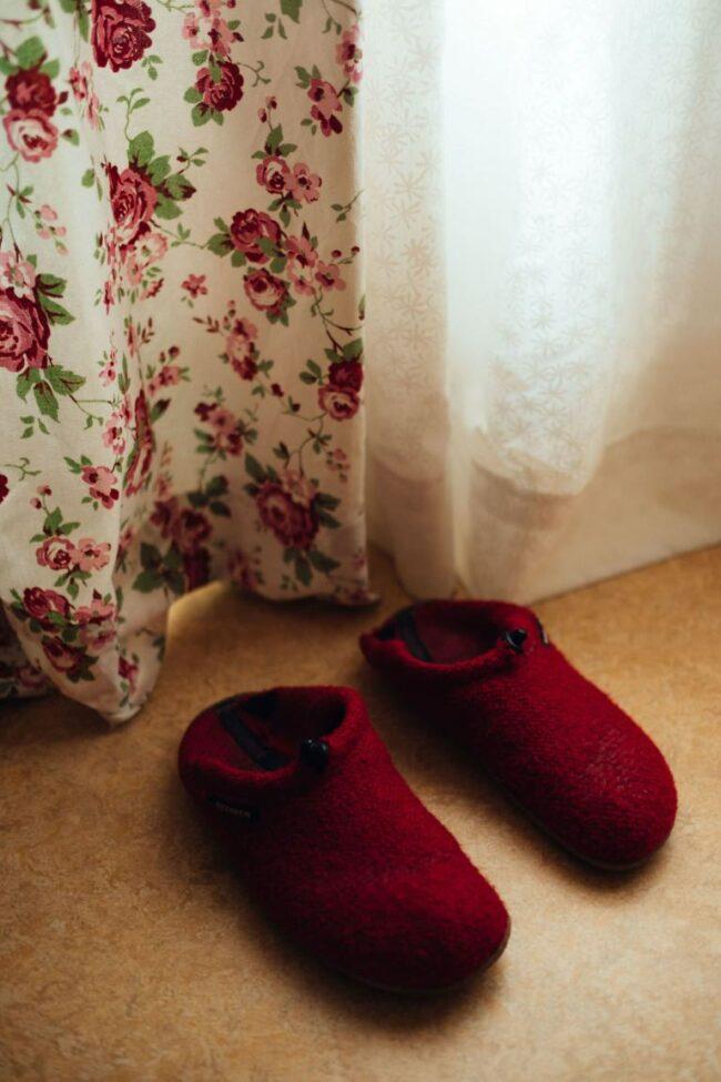 Rote Hausschuhe an einer Gardine