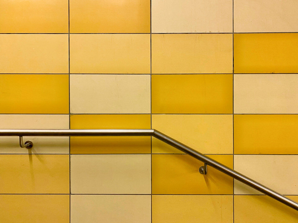 Gelbe Fließen an einer Wand mit Geländer
