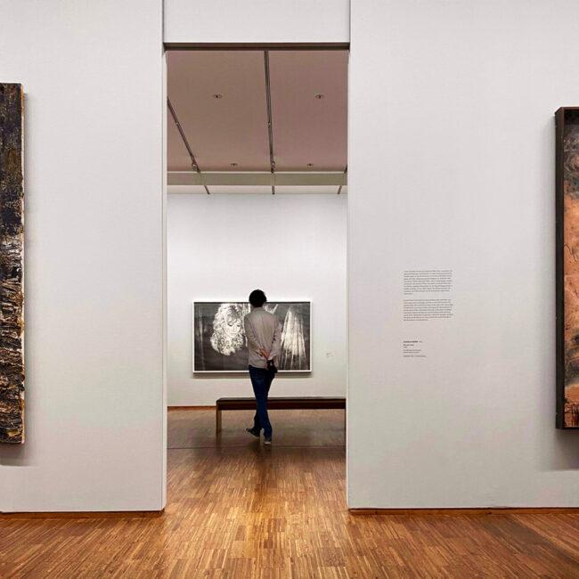 Person berachtet in einem Museum ein Gemälde