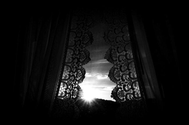 Blick auf die Sonne zwischen Vorhängen hindurch