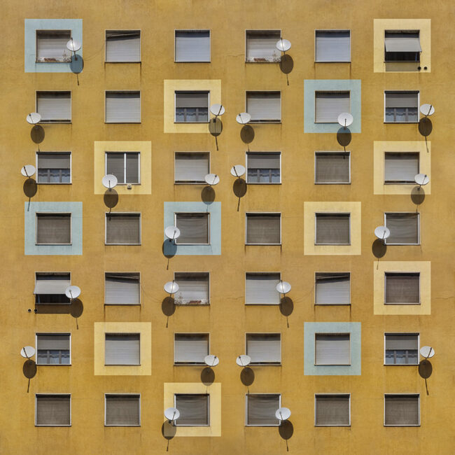 Hauswand mit vielen Fenstern und Satellitenschüsseln