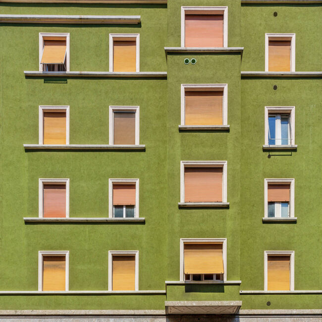 Eine Grüne Hausfassade mit orangen Fenstern