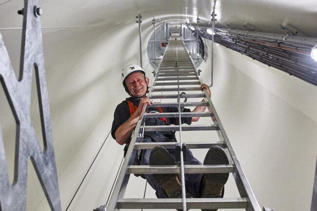 Mann steht mit Helm auf einer Leiter in einer Röhre