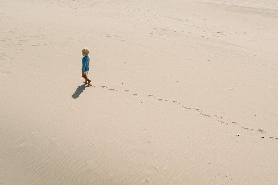 Kind läuft im Sand