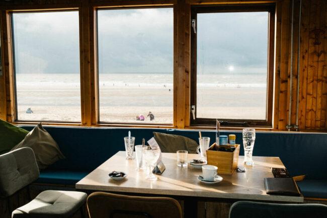 Frühstückstisch mit Fensterfront, die den Blick aufs Meer zeigt