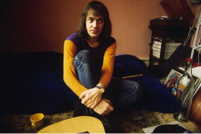 Portrait von Udo Lindenberg. Er seitzt auf dem Boden in einem Zimmer