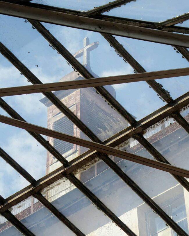 Blick durch ein Dachfesnter auf einen Kirchturm