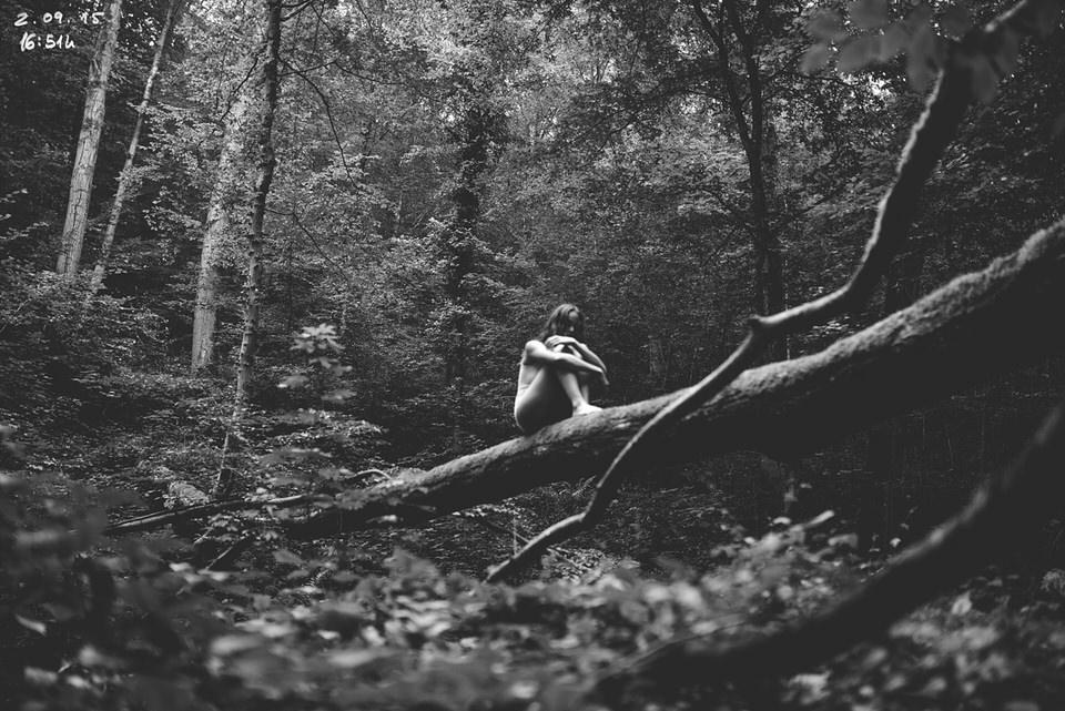 Nackte Person auf einem Baumstamm