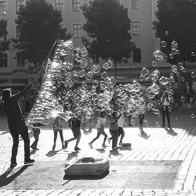 Kinder auf einem Platz mit einer Person die Seifenblasen macht