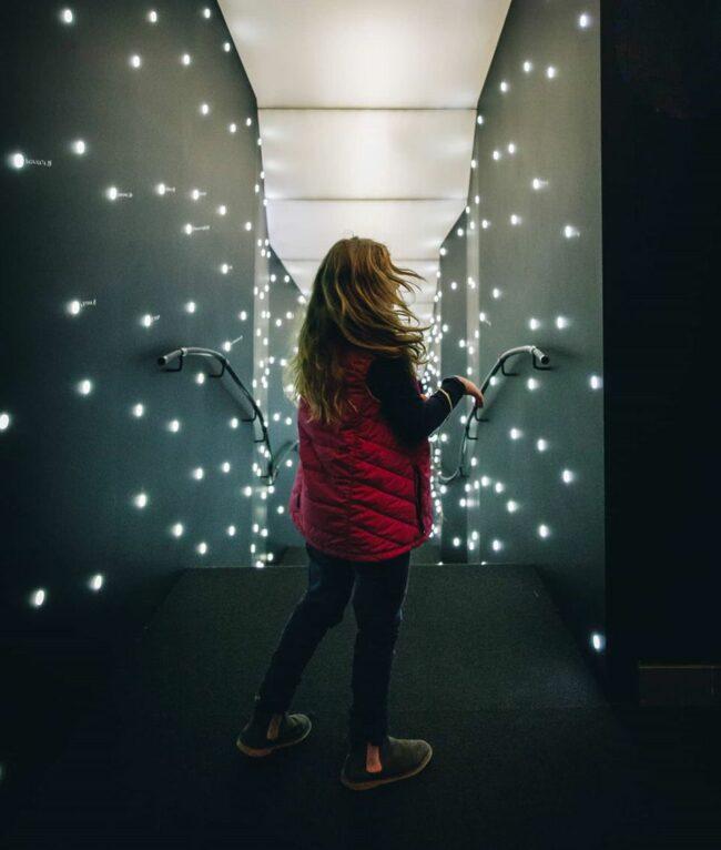 Kind in einem Flur voller Lichter