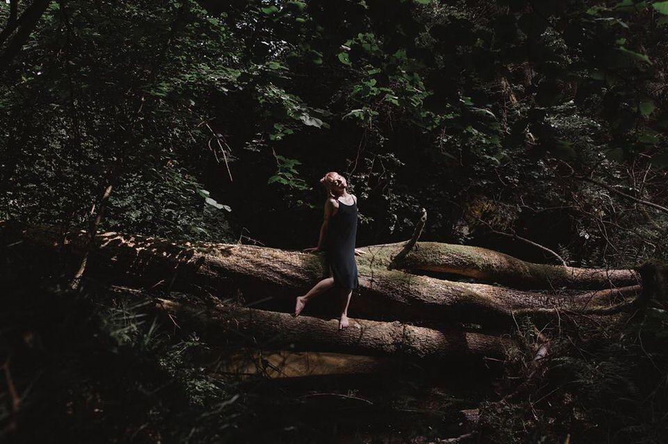 Frau balanciert auf umgefallenen Stämmen