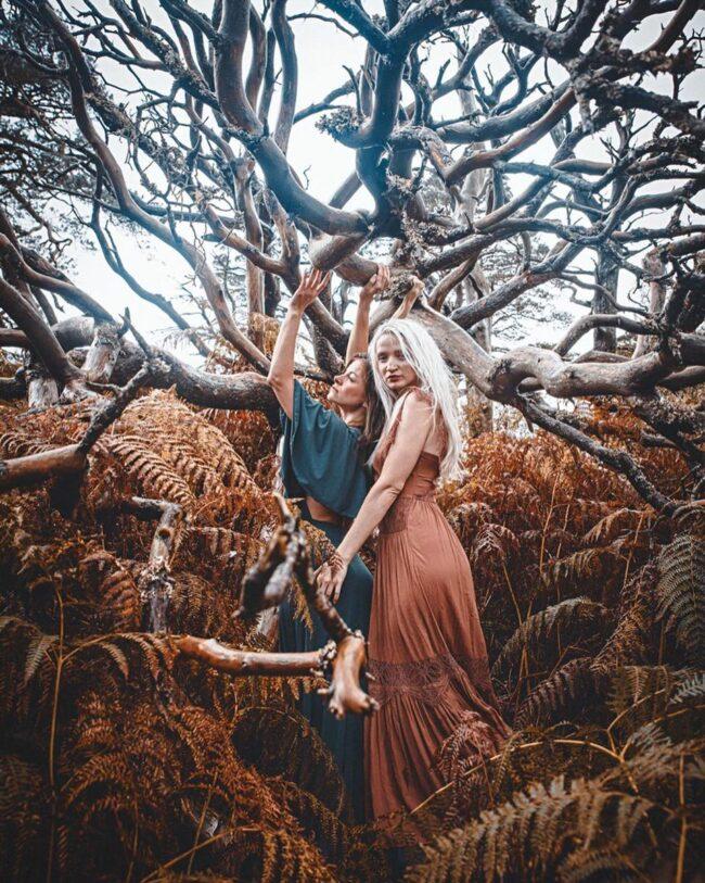 Zwei Frauen posieren an einem kahlen Baum
