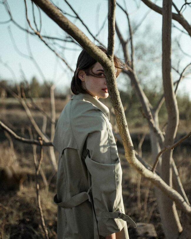 Eine Frau zwischen kahlen Bäumen