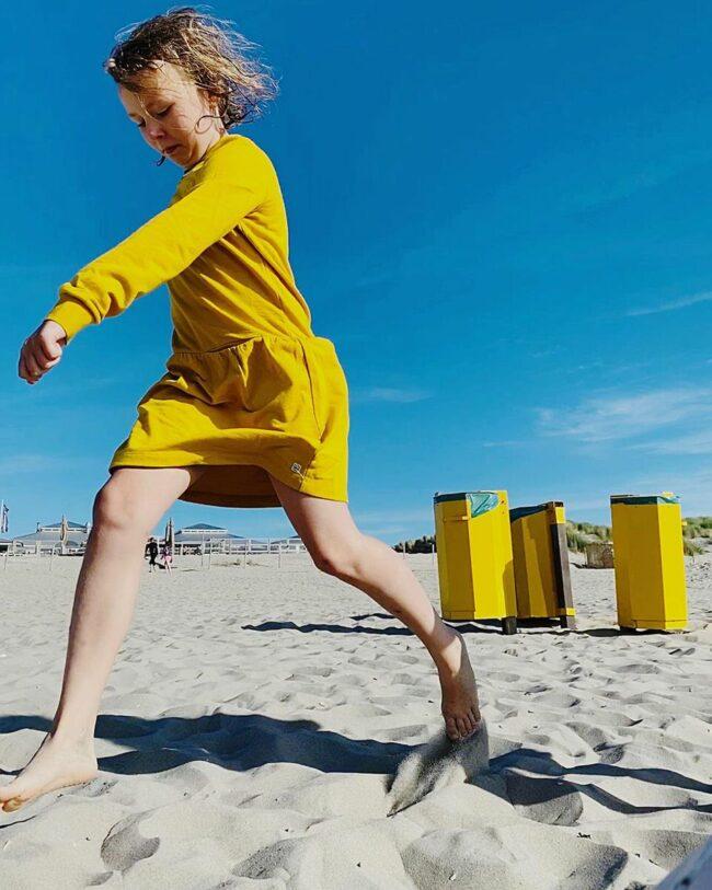 Kind im gelben Kleid vor gelben Mülltonnen am Strand