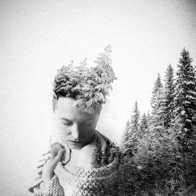 surreale Doppelbelichtung einer Frau und einem verschneiten Wald