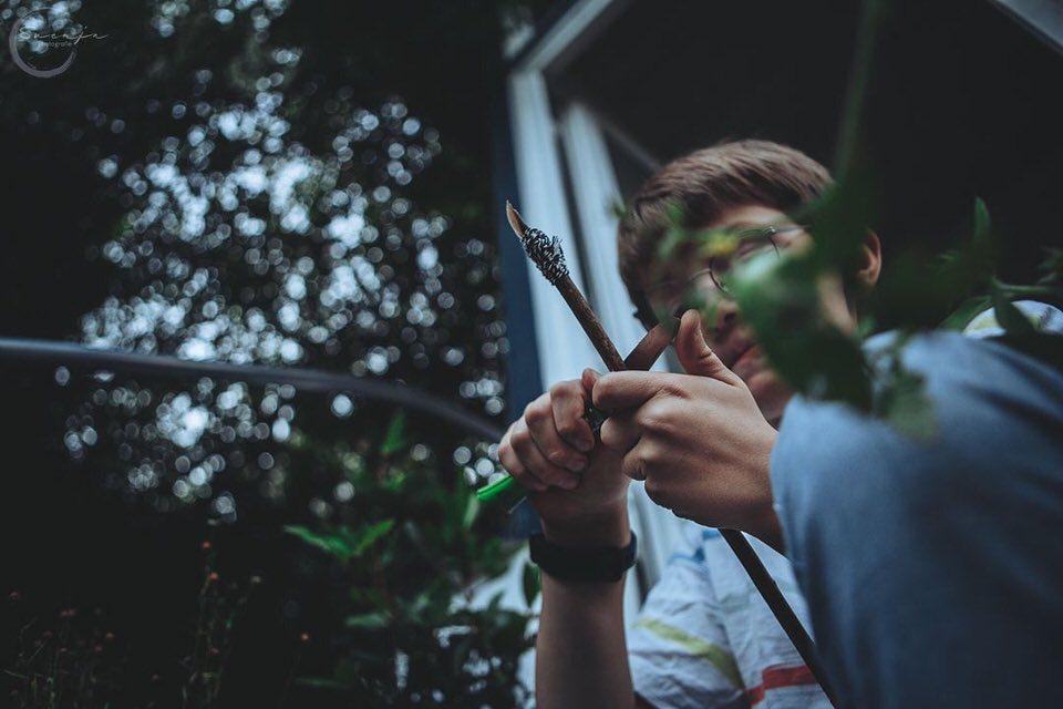 Kind schnitzt einen Zweig