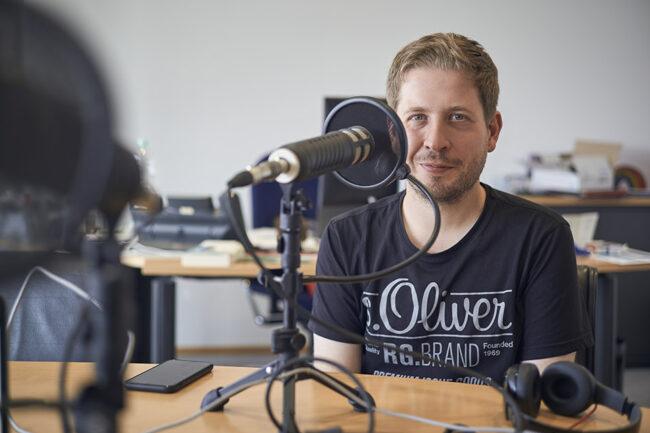 Kevin Kühnert sitzt am Konferenztisch hinter einem Mikrofon bei der Aufnahme des Kwerfeldein Podcasts im Willy-Brandt-Haus