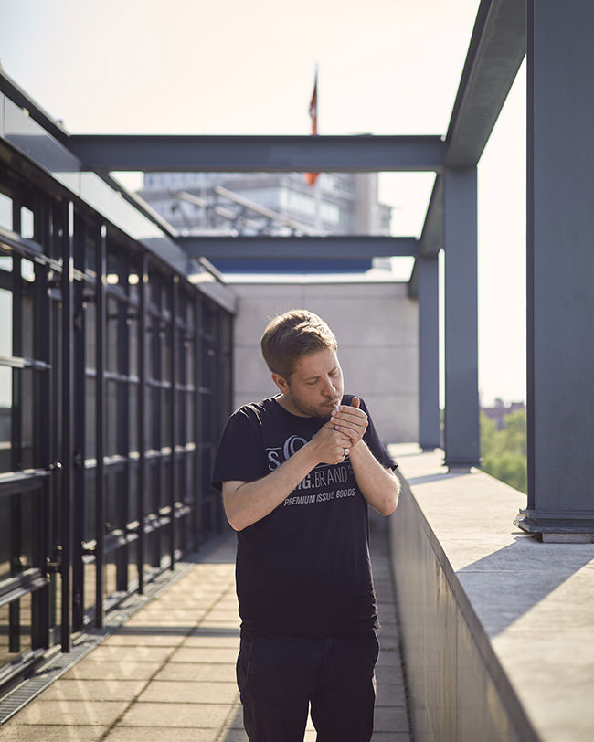 Kevin Kühnert zündet sich eine Zigarette an auf der Terrasse des Willy-Brandt-Hauses