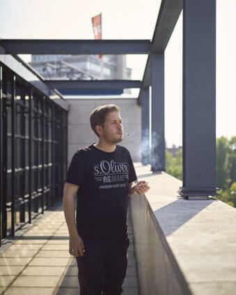 Kevin Kühnert steht mit Zigarette im Mund auf der Terrasse des Willy-Brandt-Hauses und schaut auf die Straße