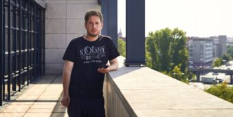 Mann steht mit Zigarette und Handy in der Hand auf einer Terrasse.