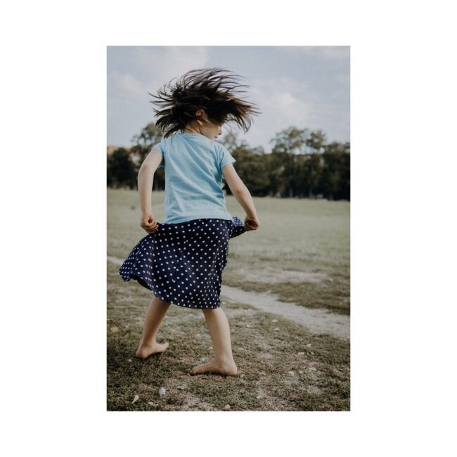 Kind tanzt auf der Wiese