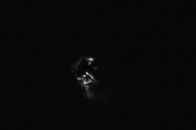 Gesicht teilweise beleuchtet vor einem schwarzen Hintergrund