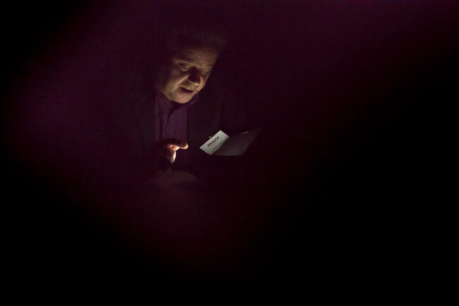 Mann im Dunkeln beleuchtet von einem Display