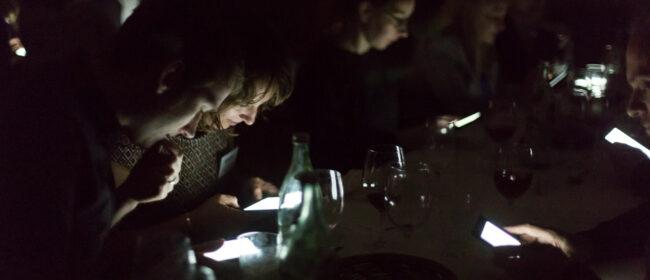 Menschen im Dunkeln, beleuchtet von Displays