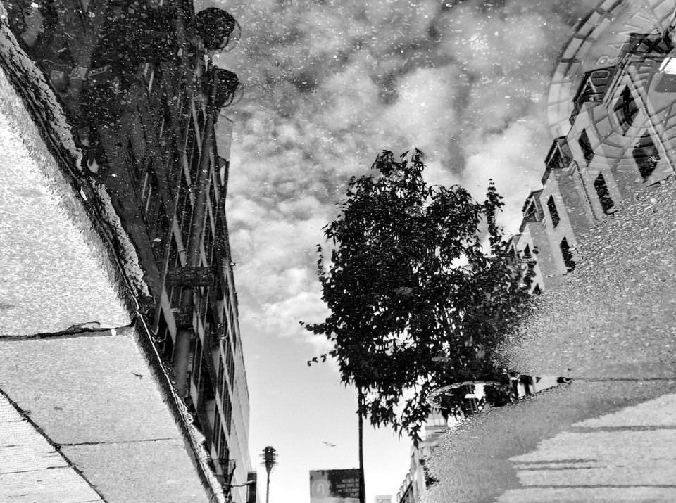 Straßenszene spiegelt sich in einer Pfütze