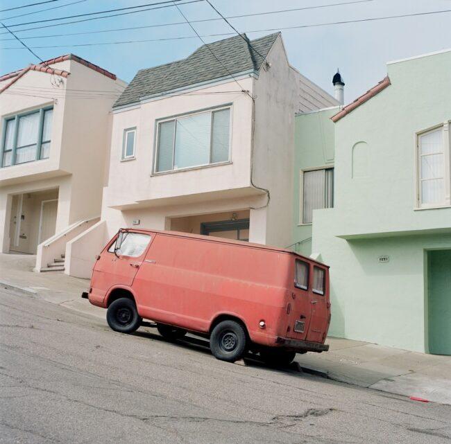 roter Transporter in einer steil bergauf führenden Straße