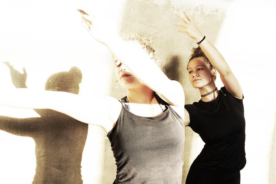 Zwei Frauen tanzen und werfen Schatten an die Wand