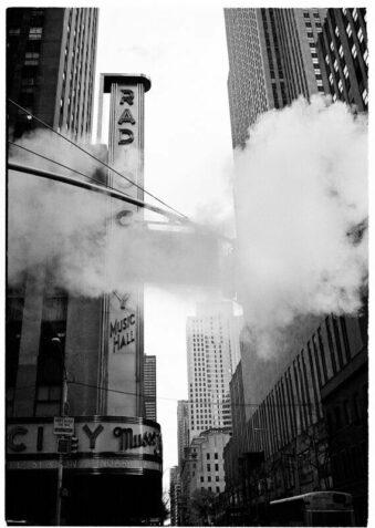 Schwarzweiß-Aufnahme von Hochhäusern und einer Rauchwolke