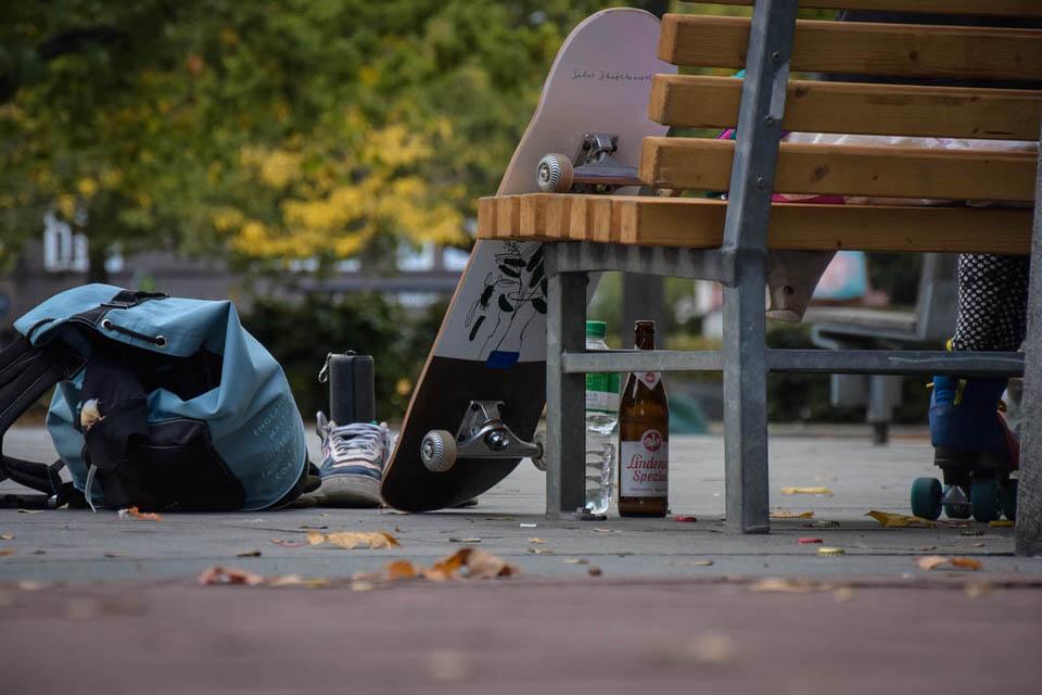 Skateboad lehnt an einer Bank, in Schuhen davor steht eine Musikbox