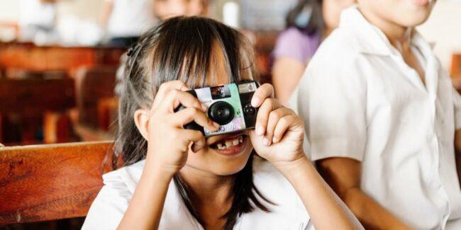 Mädchen schaut lachend durch eine Kamera