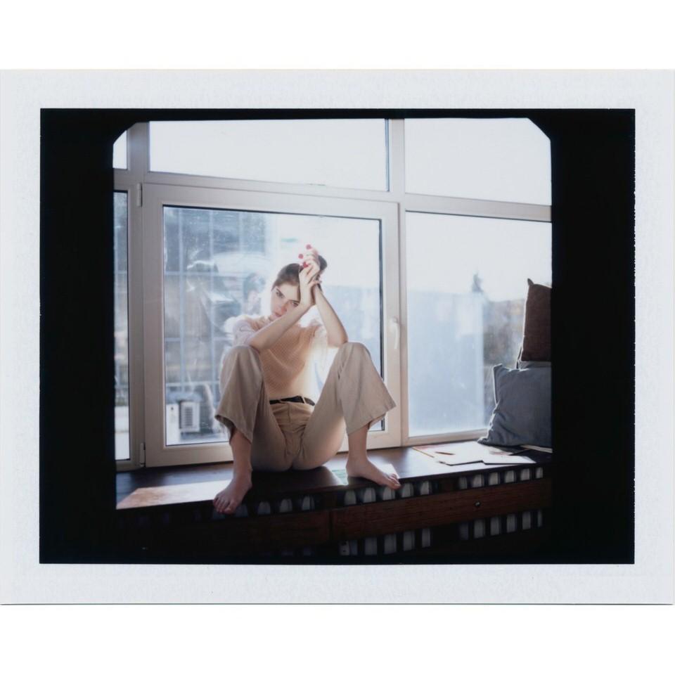 Frau sitzt auf einem Fensterbrett