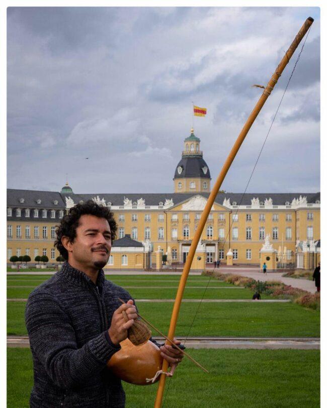 Person vor einem Schloss mit Instrument