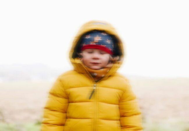Kind in gelber Jacke leicht unscharf
