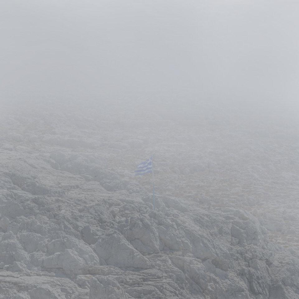 griechische Fahne auf Felsen im Nebel