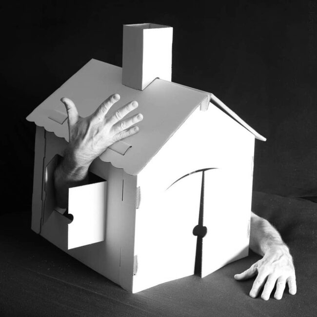 Hände kommen aus einem Papphaus