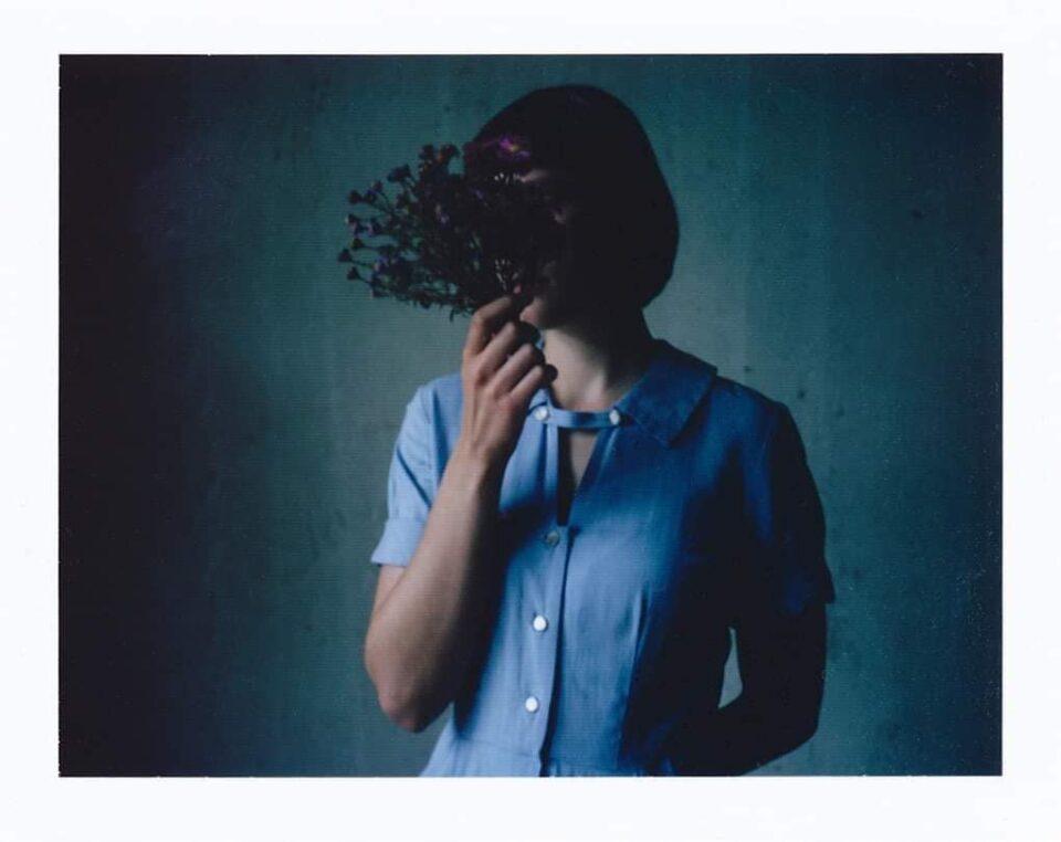 Frau hält sich Blumen vor das Gesicht