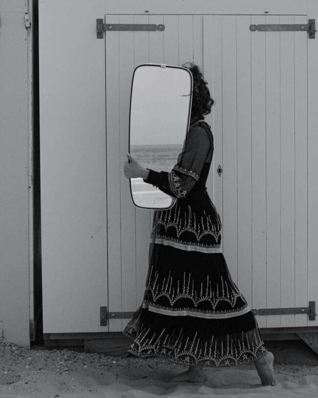 Person trägt Spiegel vor dem Gesicht