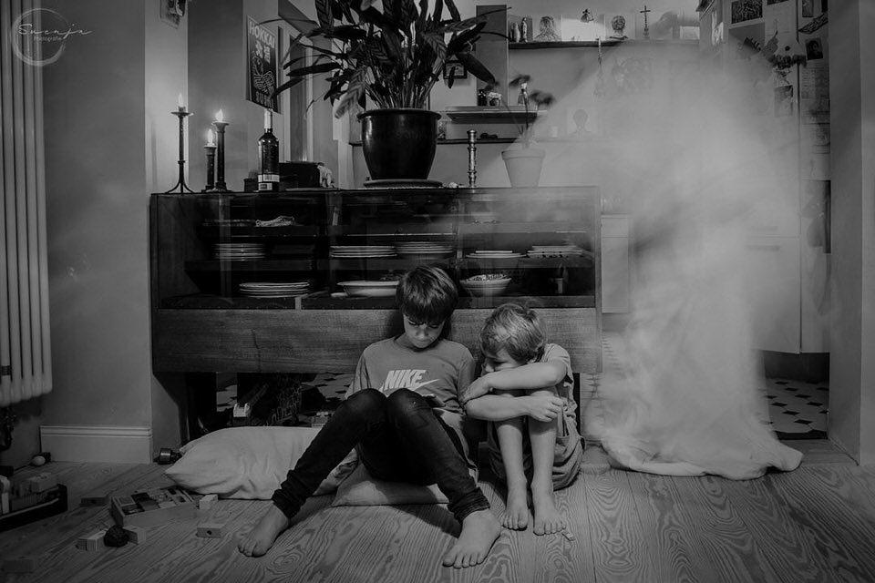Zwei Kinder verstecken sich vor einem Geist hinter dem Sofa