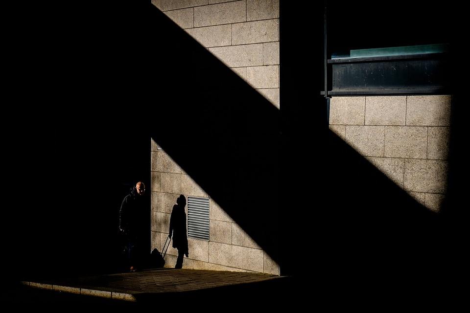 Mensch und Schatten auf einer Hausfassade