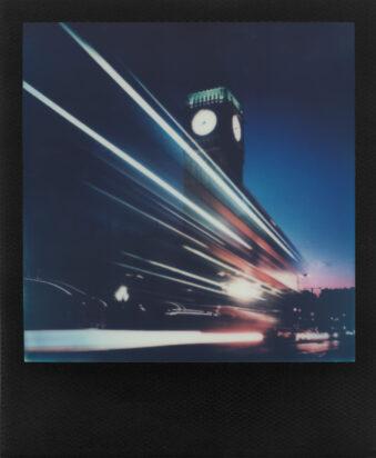 schwarzes Polaroid, Lichtspuren vor erleuchteter Turmuhr