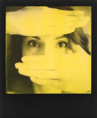 schwarzes Polaroid, Portrait mit vorgehaltenen Händen